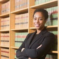 Headshot of a Black woman with short hair leaning on a bookshelf