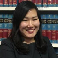 Headshot of an Asian woman with shoulder-length black hair in front of a bookshelf