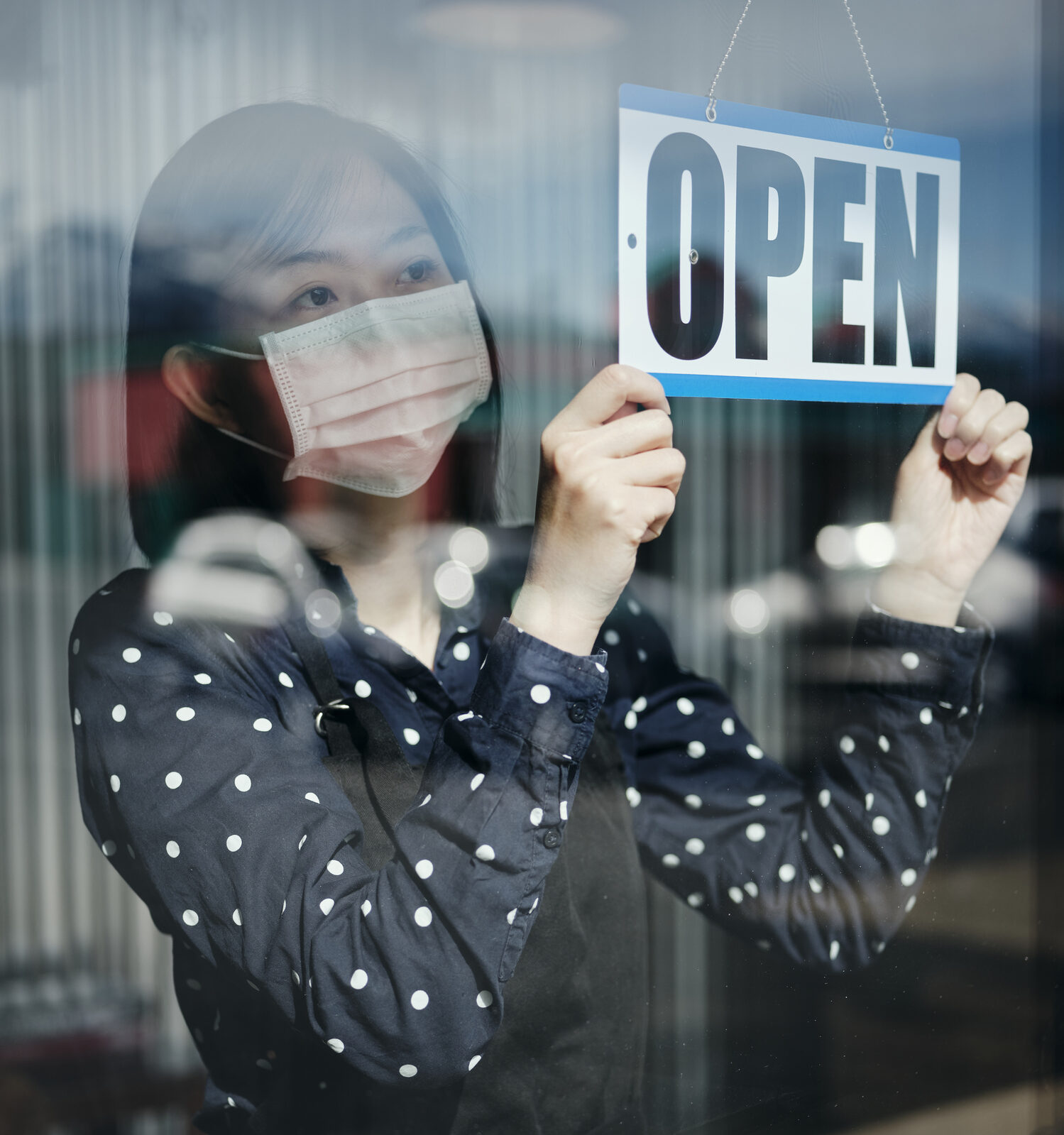 """Image of a masked and gloved woman holding an """"Open"""" sign behind a storefront window"""
